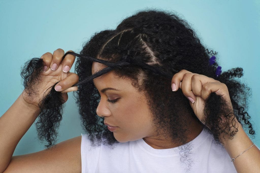 woman creating braid on natural hair