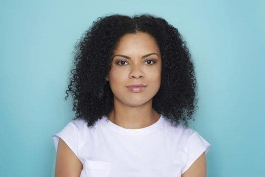 woman with curly hair worn down preparing for natural braids hairstyle tutorial