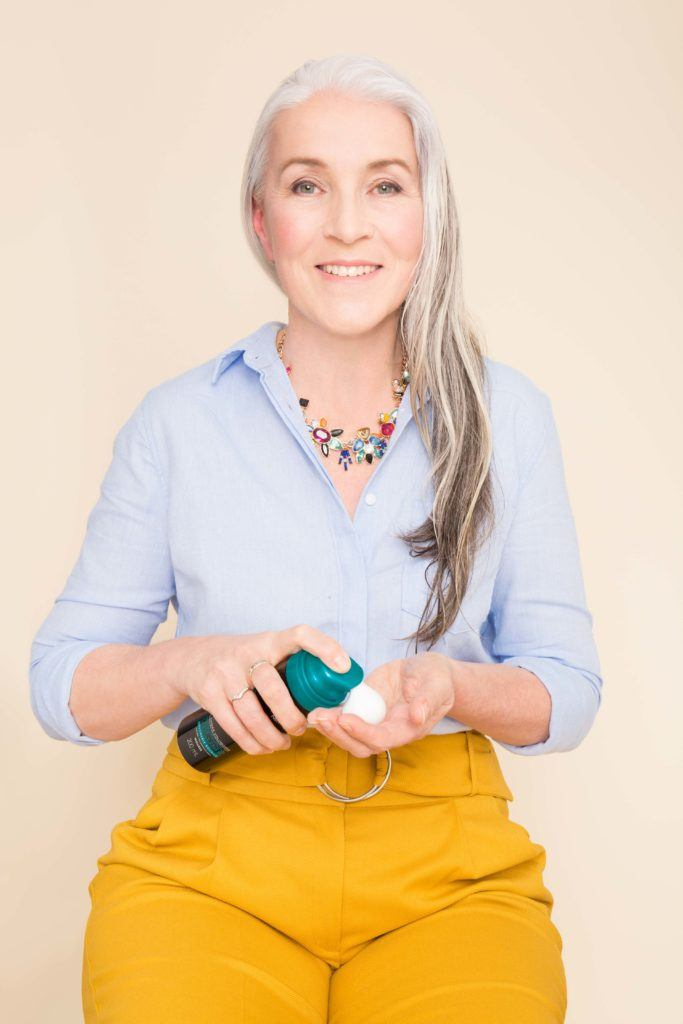 ponytail for women over 50: older woman adding mousse to hair
