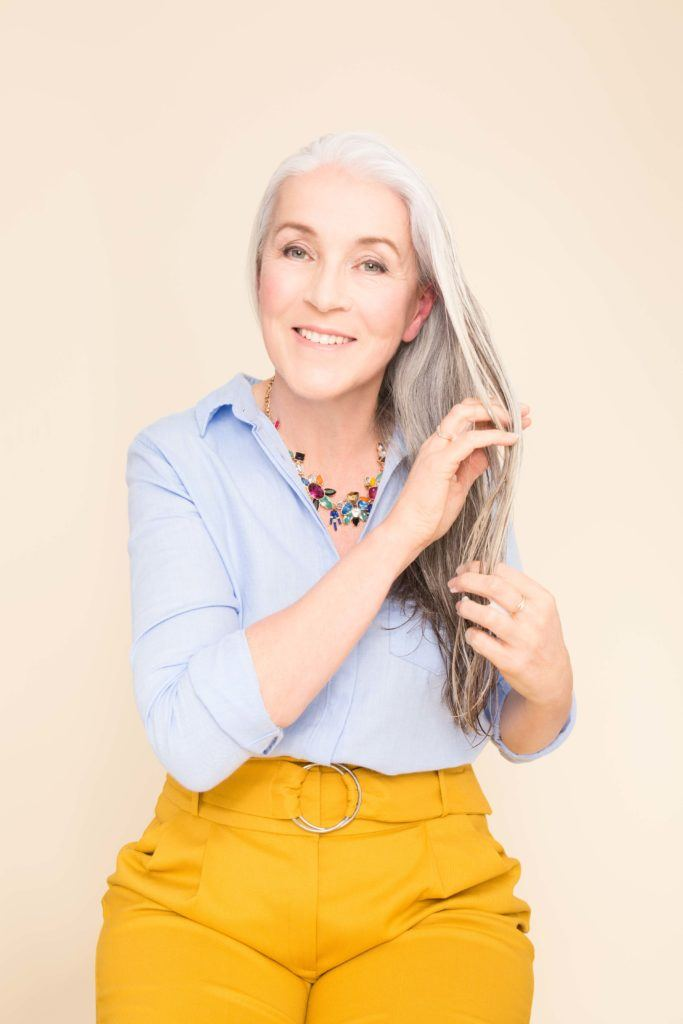 ponytail for women over 50: older woman finger combing her hair