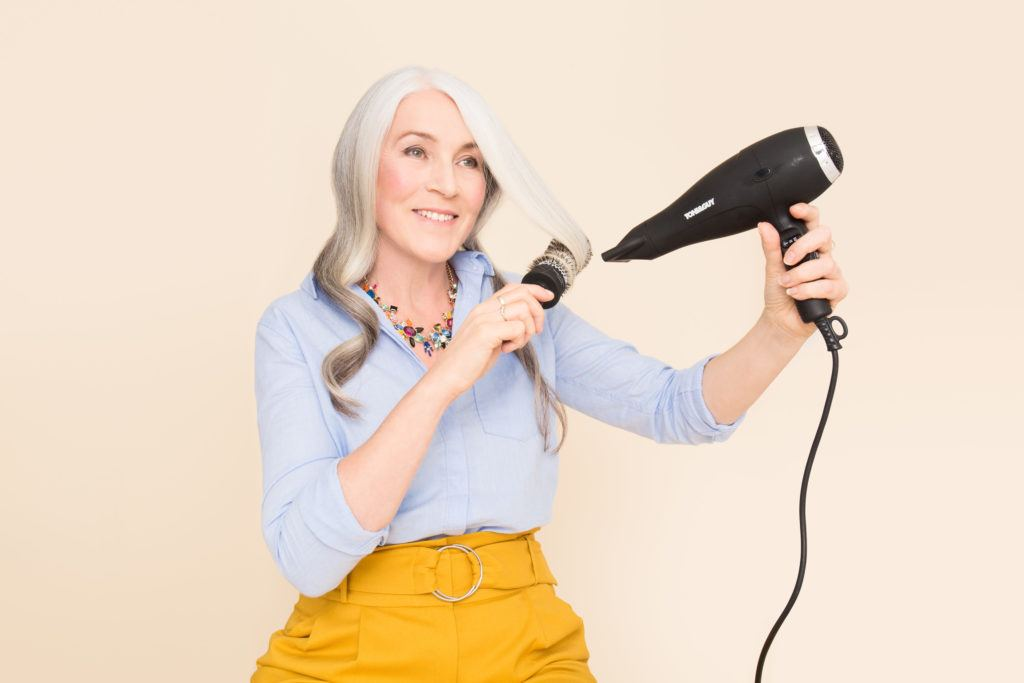 ponytail for women over 50: older woman blowdrying her hair