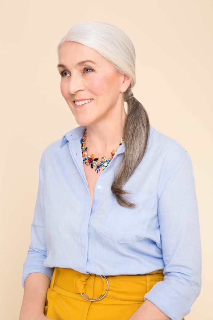 updo ponytail for women over 50: low ponytail hairstyle on older woman with grey hair