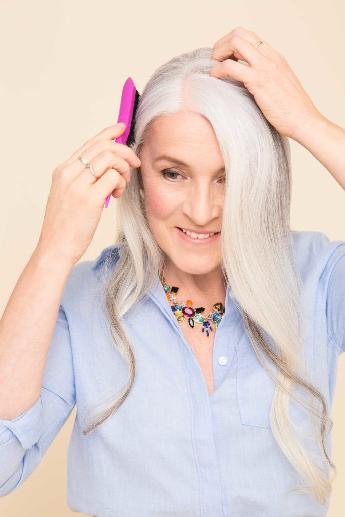 ponytail for women over 50: older woman parting hair and brush