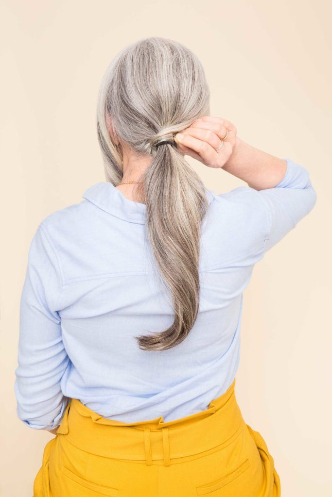 ponytail style for women over 50: older woman creating ponytail on hair