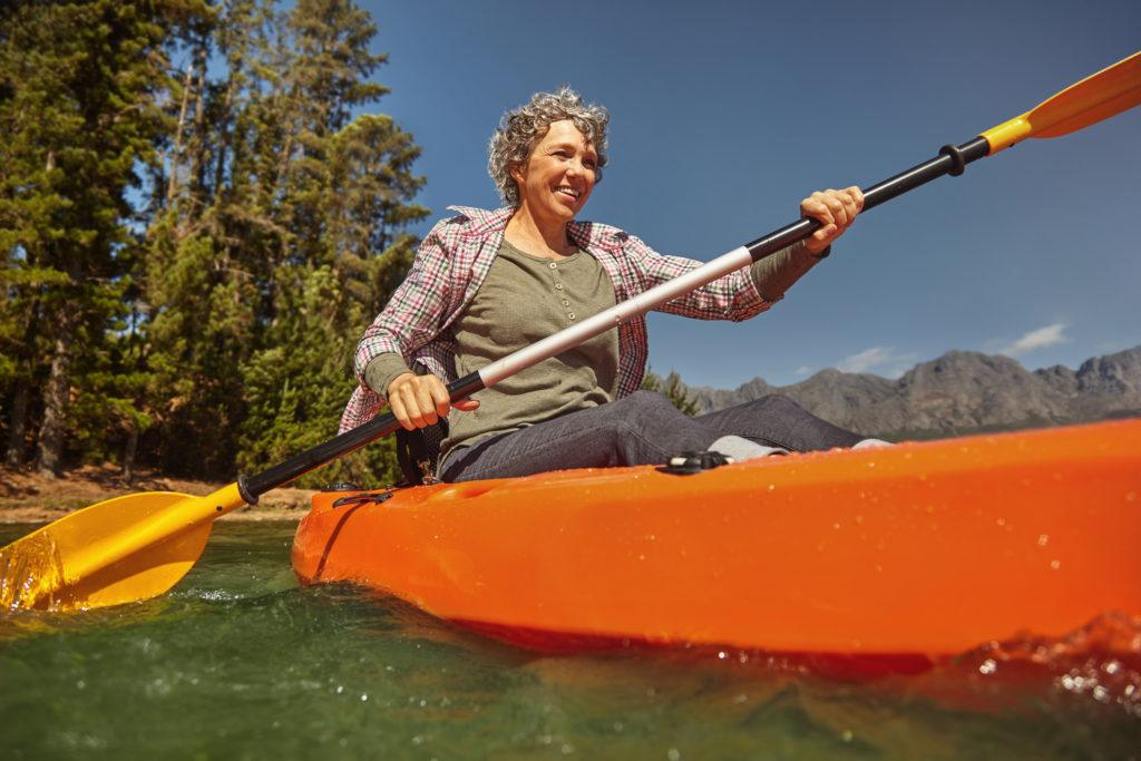 a photo of a senior woman with short grey hair kanoing on a river