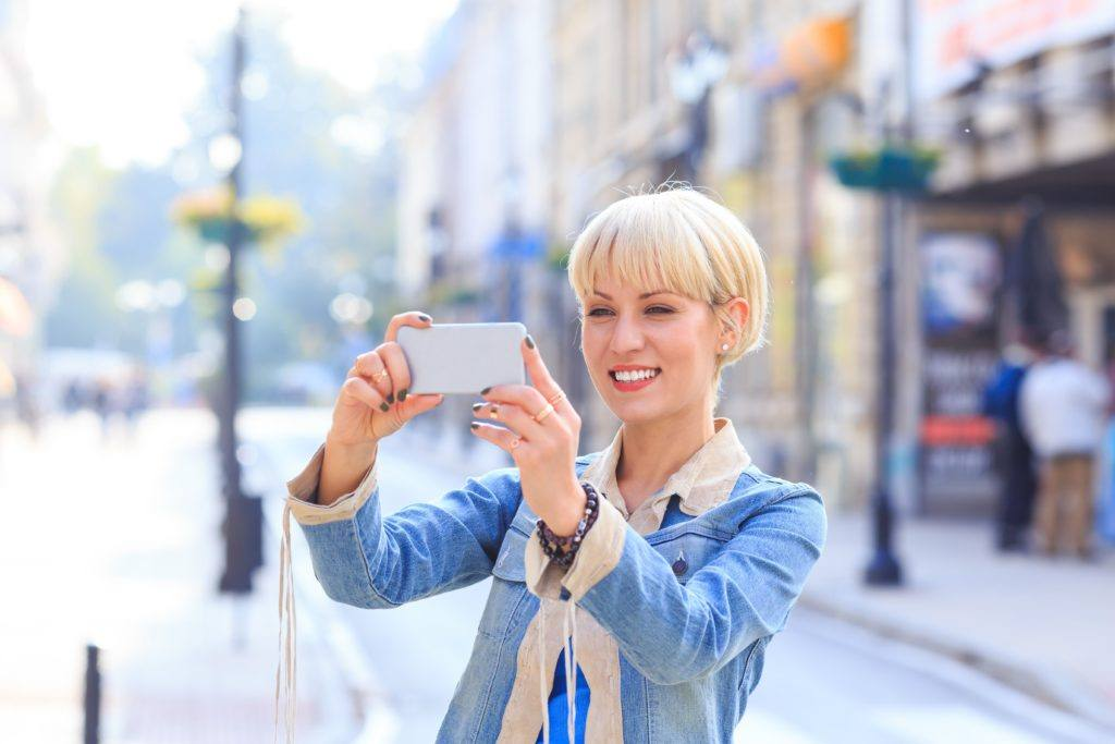 a smiling blonde woman with short bob hair wearing denim outfit taking a picture in a city