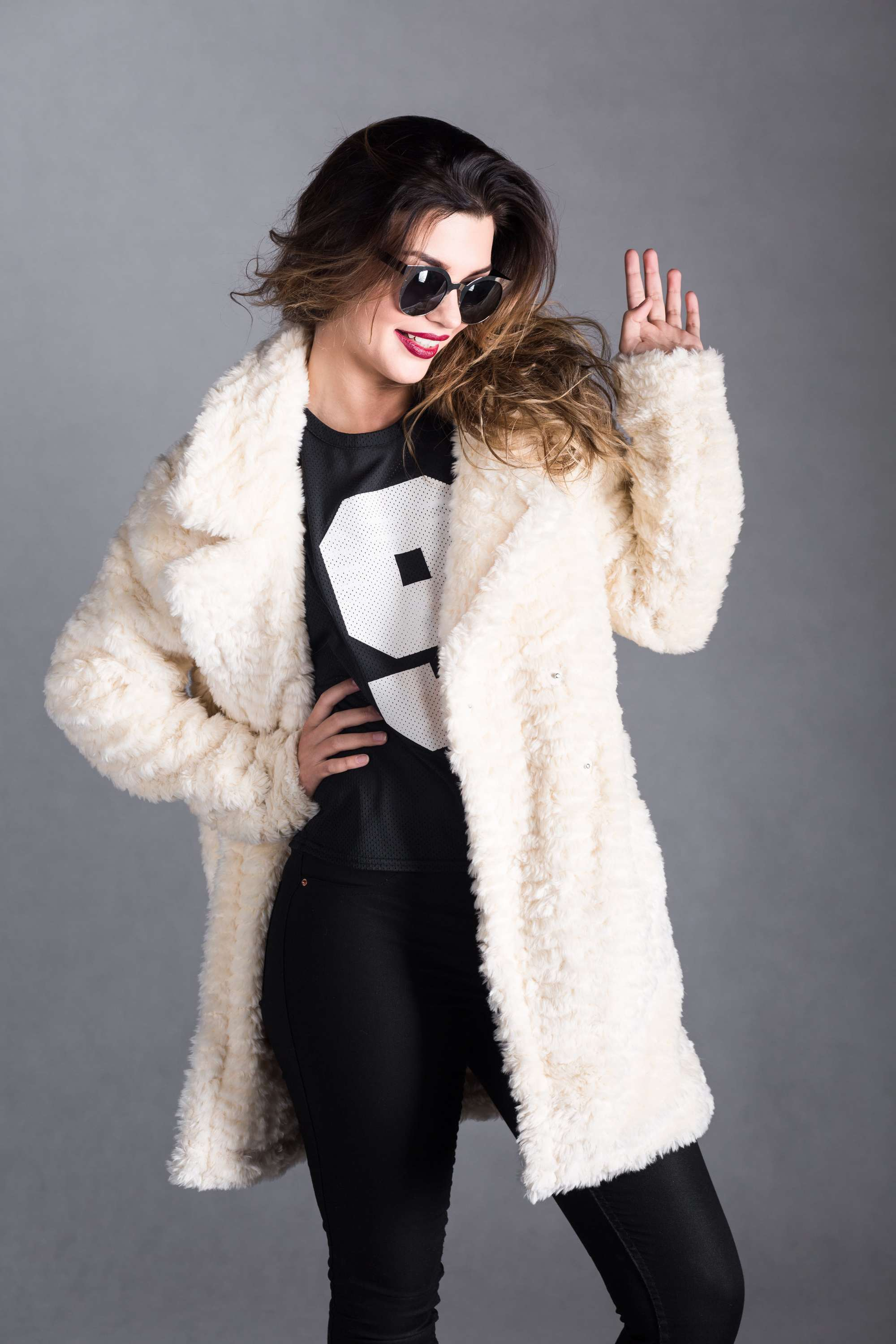 a woman standing in front of a grey background wearing a fur coat and black black outfit