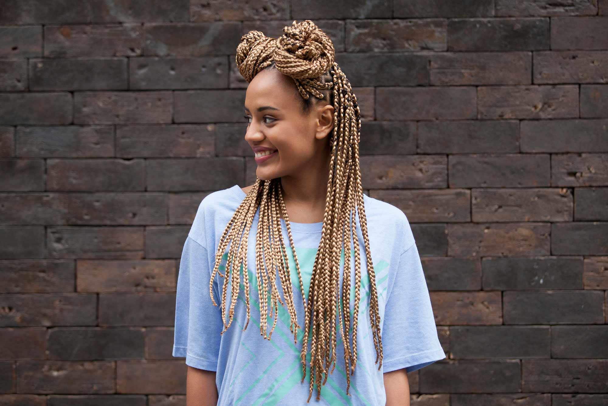 a smiling woman with two braided buns in front of a brick wall
