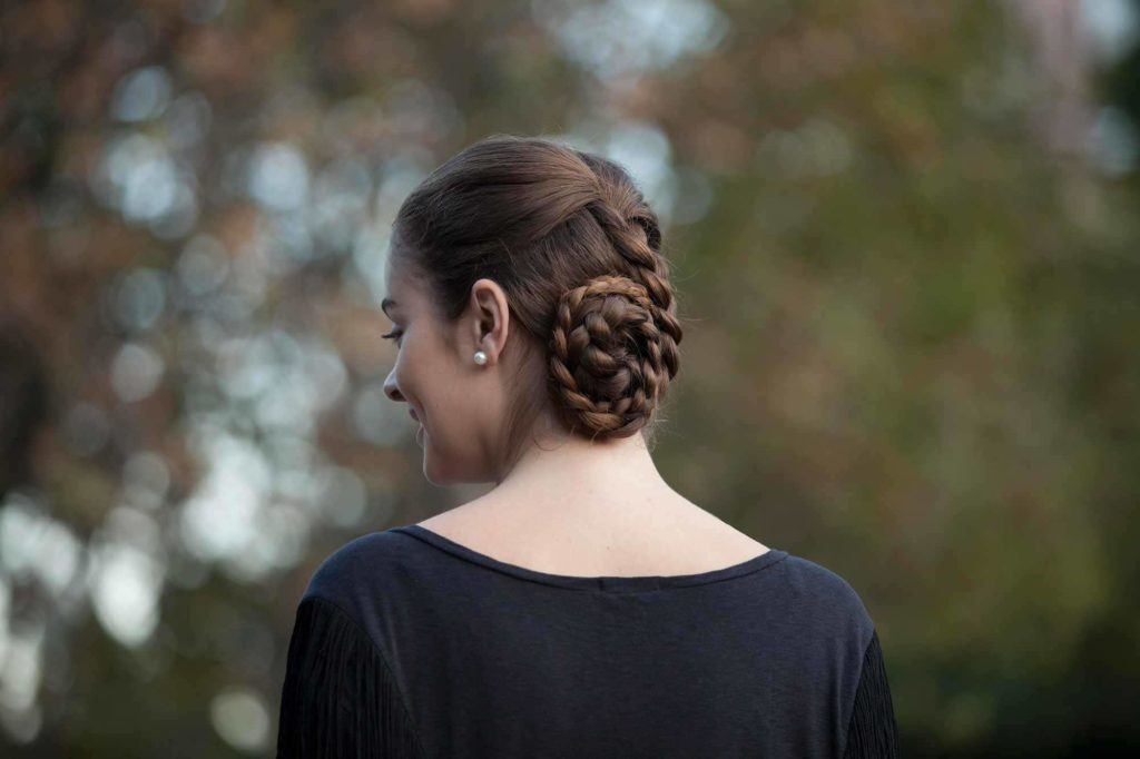 a coiled braided bun of a woman standin outside