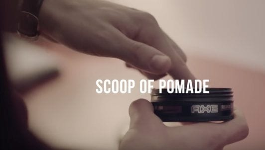 a photo of a man's hand scooping axe pomade