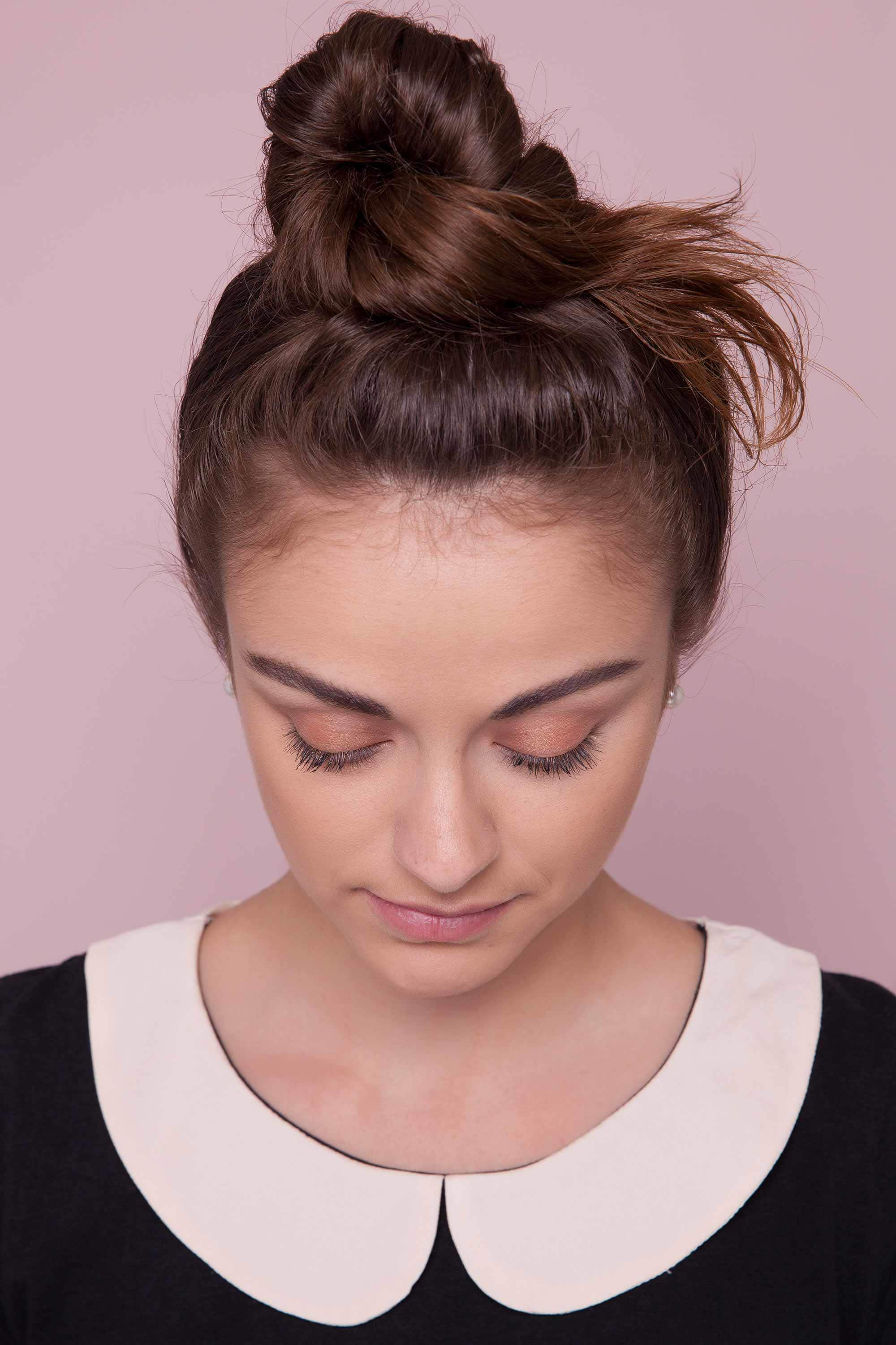 a top knotted hair woman on a pink background