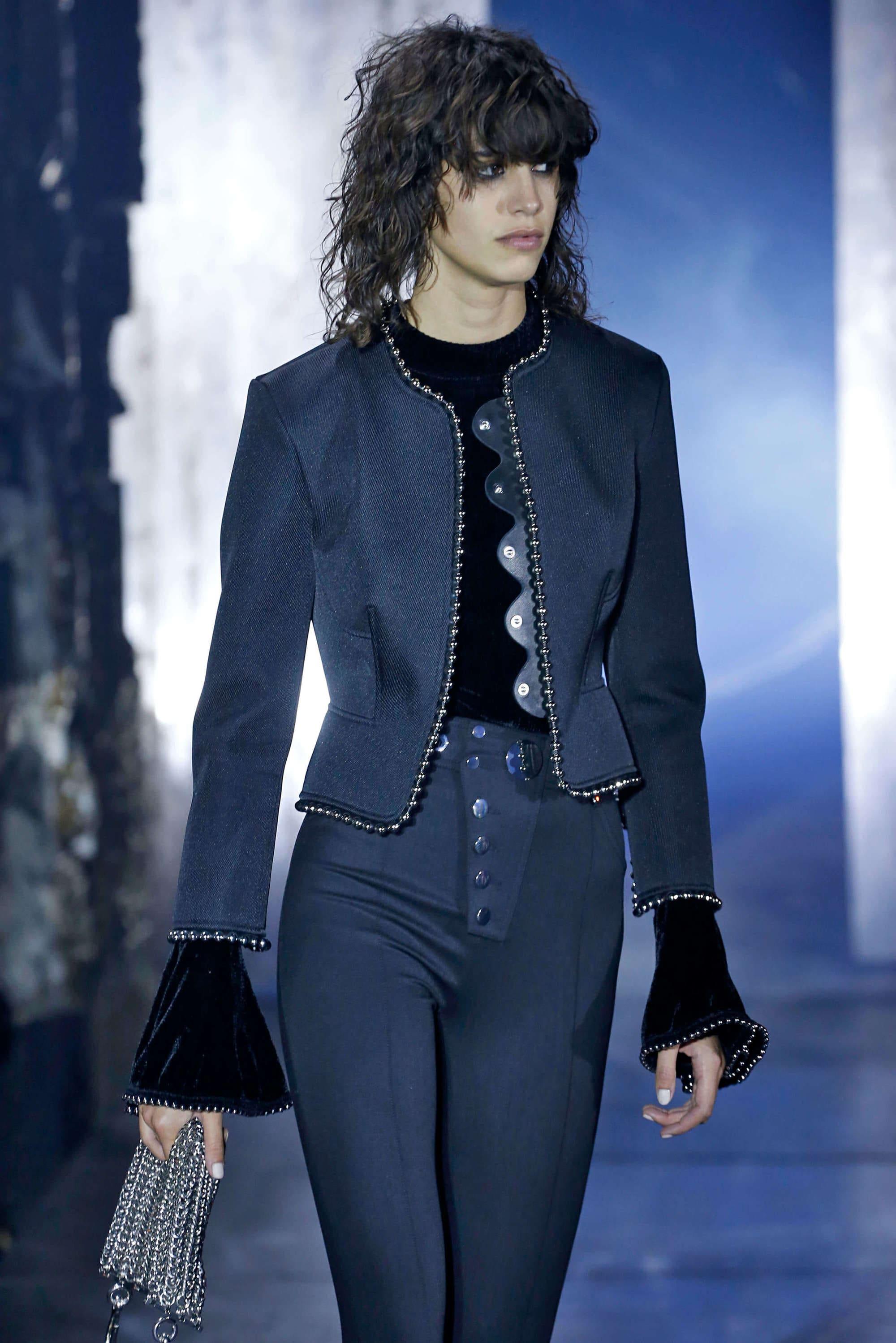 a female model with short choppy curly hair on a runway