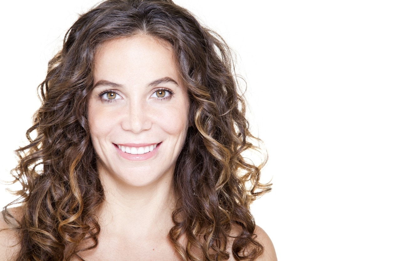 a close up look of curly brown hair woman smiling on the white background