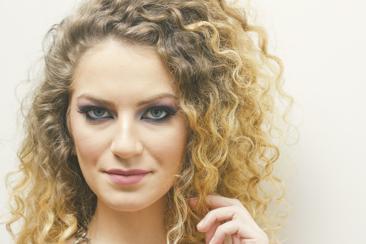 a strong look of a curly blonde woman on white background