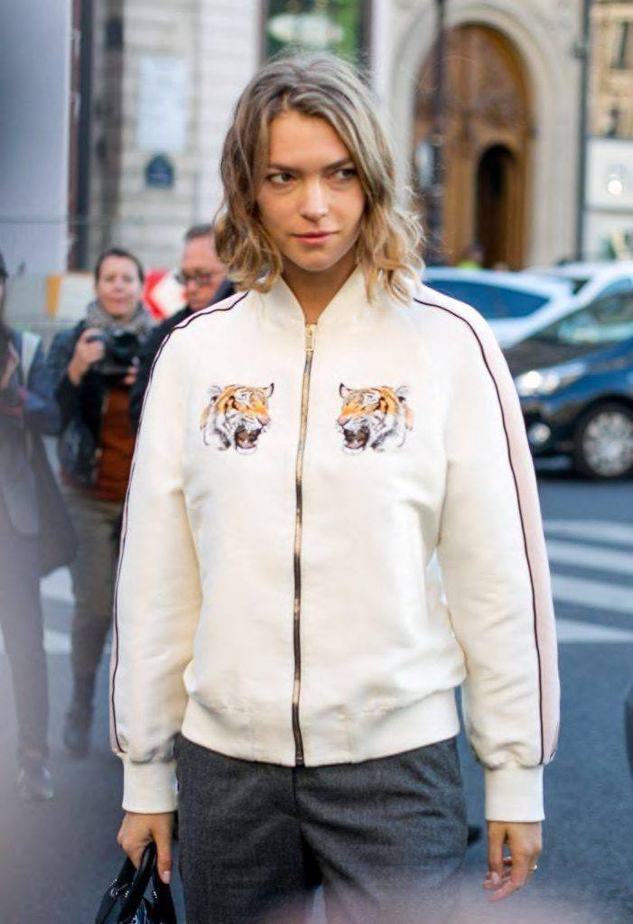 naturally wavy ombre hair of a woman wearing sporty jacket walking on a street