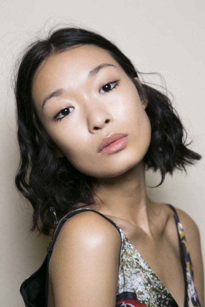 an asian woman with messed wavy hair on the light grey background
