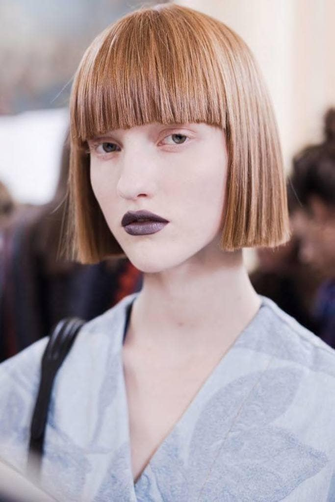a woman with a well shaped bob hair wearing dark lipstick and blue shirt standing in a crowd