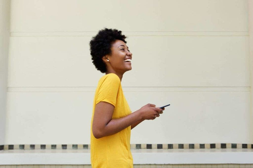 an afro woman playing her smartphone wearing yellow t-shirt in a city