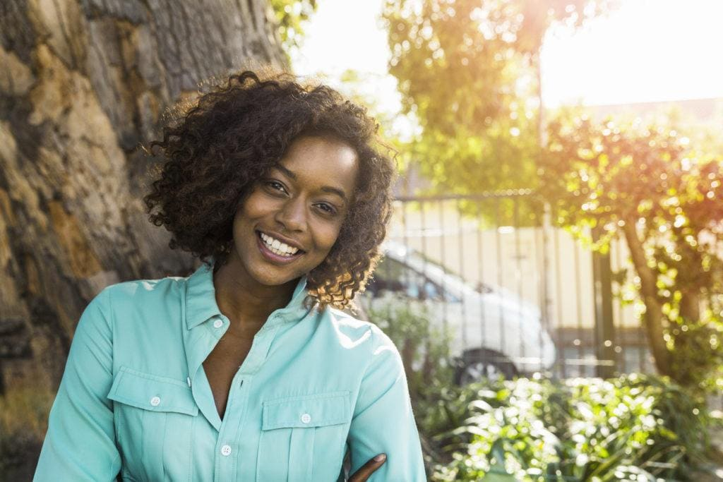 a curly short hair woman in the garden sunlighted