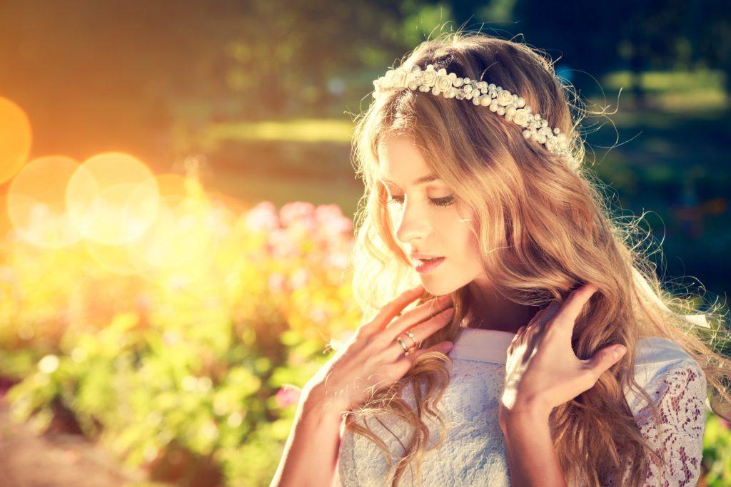 a blonde woman wearing headband posing outside highlighted by sun