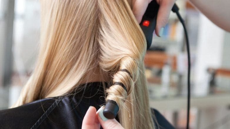 curling iron stylist long blonde hair