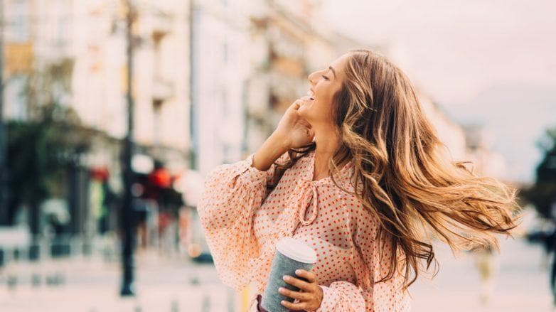 a cheerful long blonde woman holding a tumbler in a city
