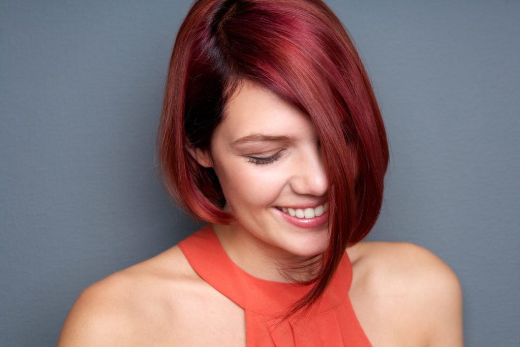 a woman with red violet hair color asymmetrical bob smiling