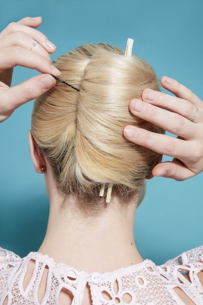 Blonde woman with a French twist updo with chopsticks in, adding bobby pins