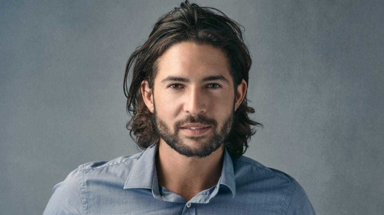 a closeup look of a bearded long hair man on grey baclground wearing blue shirt\