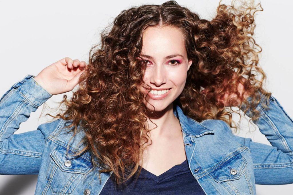 a cheerful woman wearing denim jacket with brown curly hair