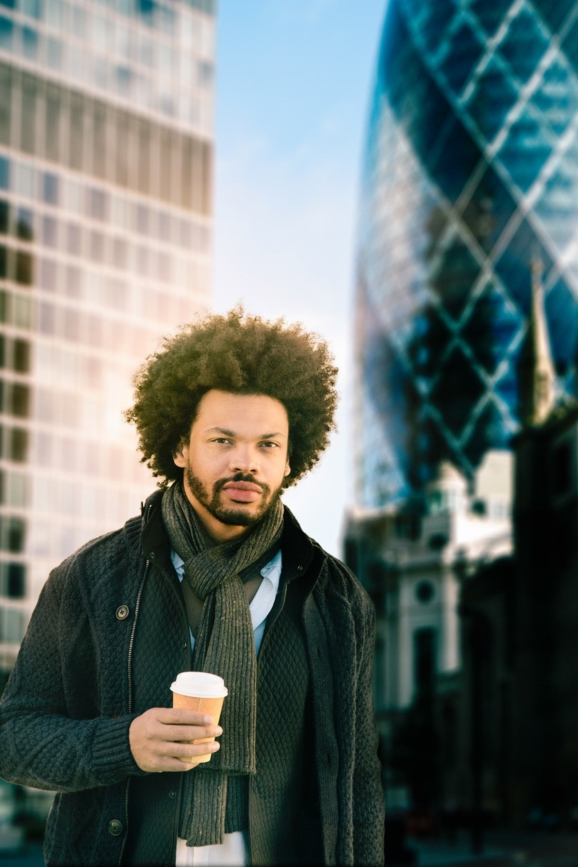 an afro man walking in a city while handling a coffee cup