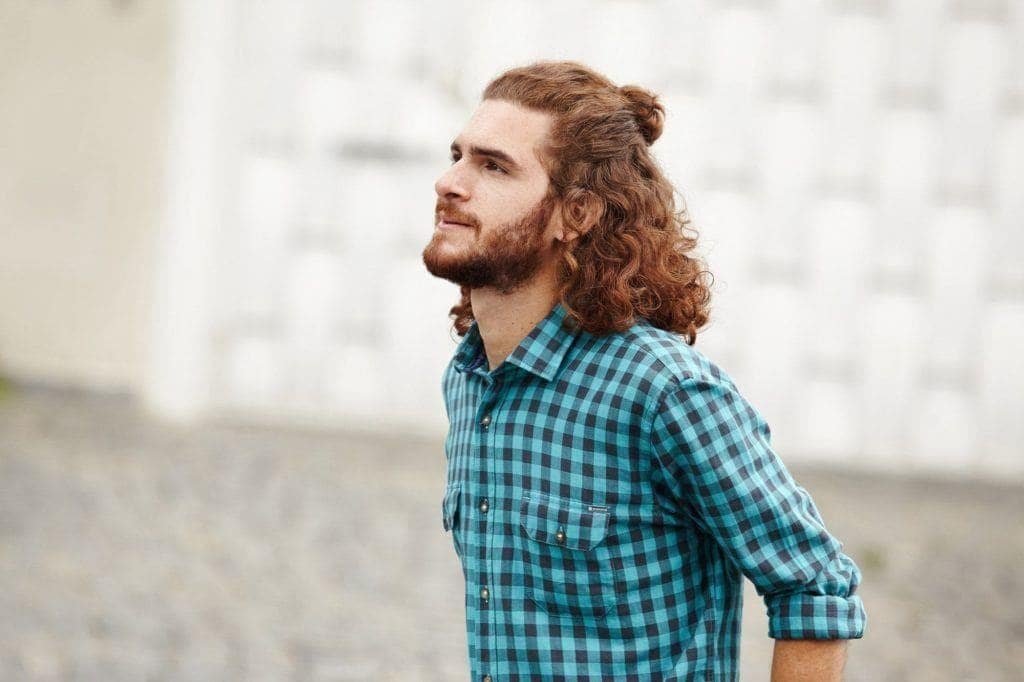 hairstyles for men with curly hair: half up man bun