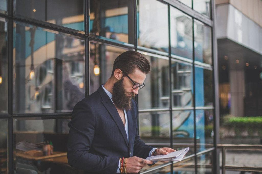 a bearded man with wet look slickback hair in a suit reading a newspaper