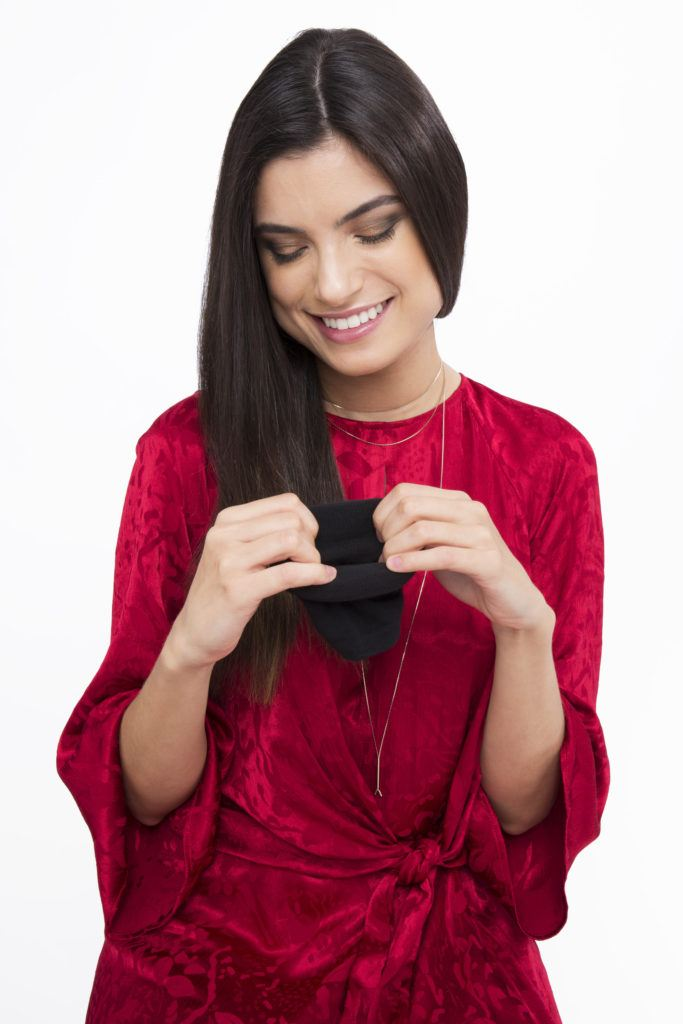 a front view of a long hair woman stretching out a sock in a red dress