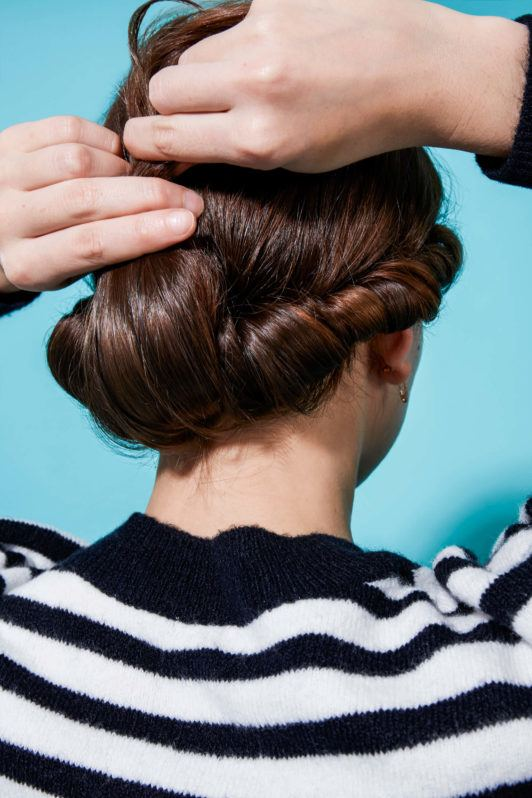 a woman making braided hairstyle