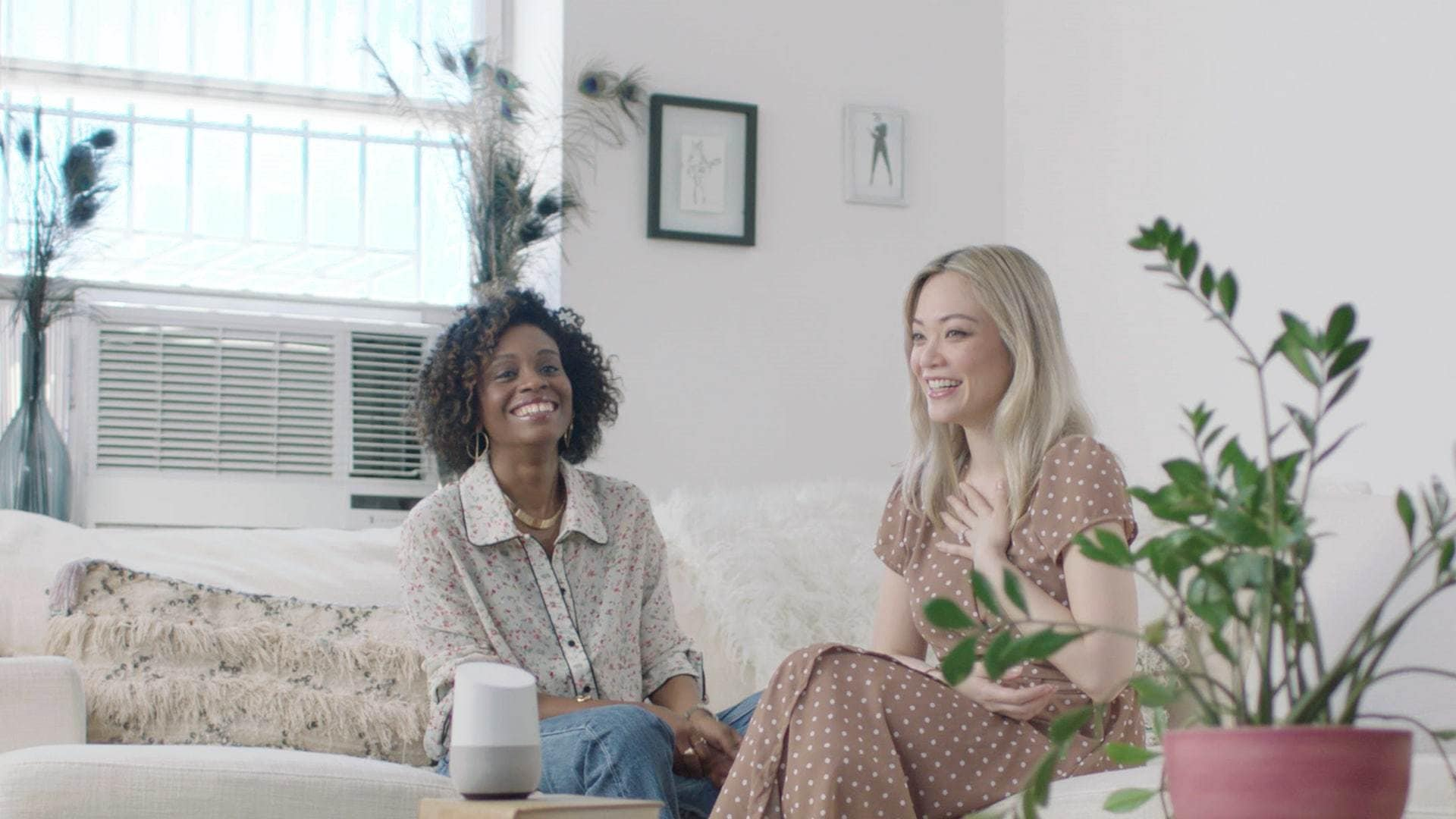two women on the sofa laughing with a Google Home Assistant device on the sofa