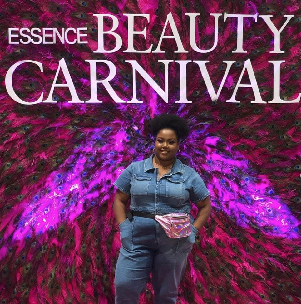 influencer at Essence Festival 2019 standing in front of a billboard