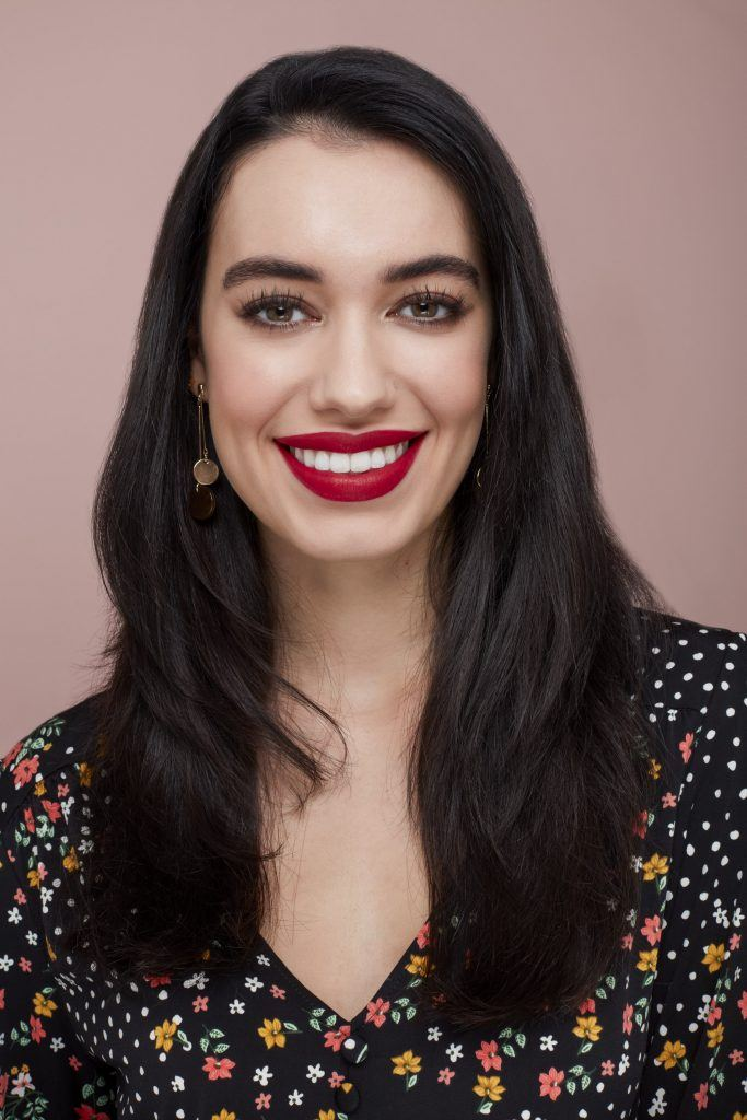 woman with long dark brown hair wearing red lipstick and a patterned top
