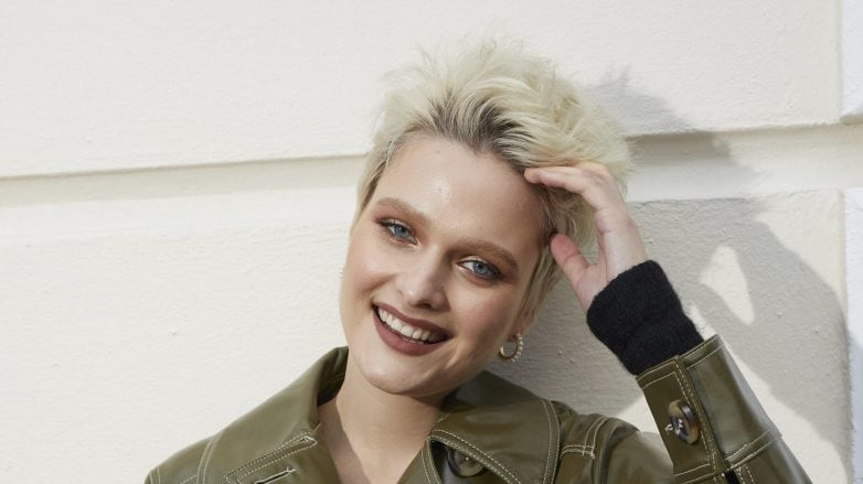 woman with short blonde hair in quiff pixie style wearing a green leather coat