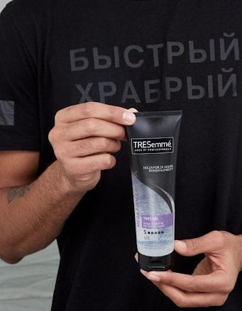 Fair skinned male holding TRESsemme gel