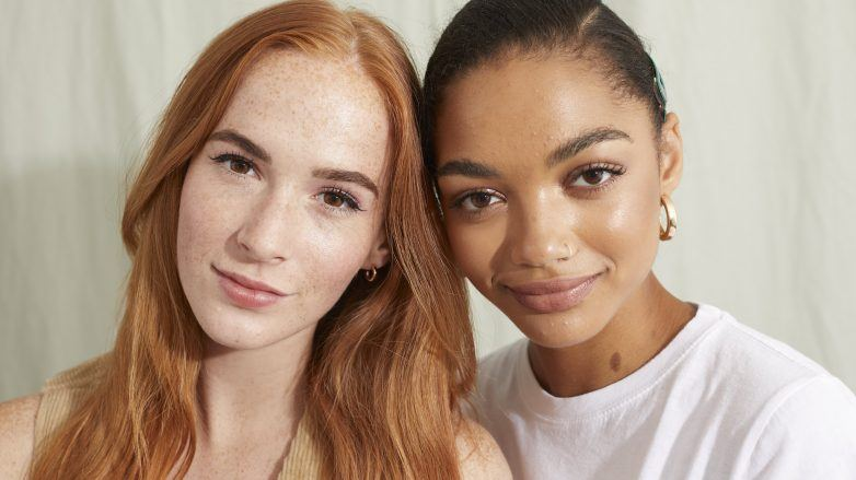 two models, one with long red hair and the other with natural hair
