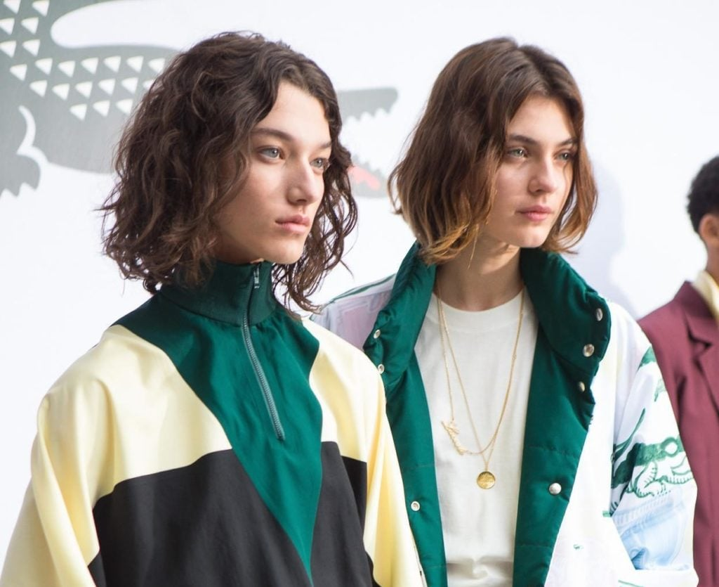 close up shot of two models backstage with wavy short hair, wearing tracksuit jackets and posing