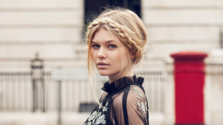 blonde woman with a milkmaid braid wearing a black lace top standing outside with a red post box in the background