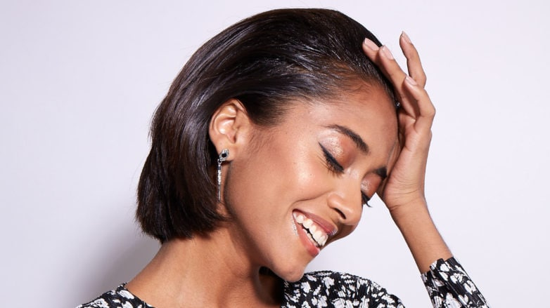 Argan oil uses and application girl with relaxed natural hair touching her head