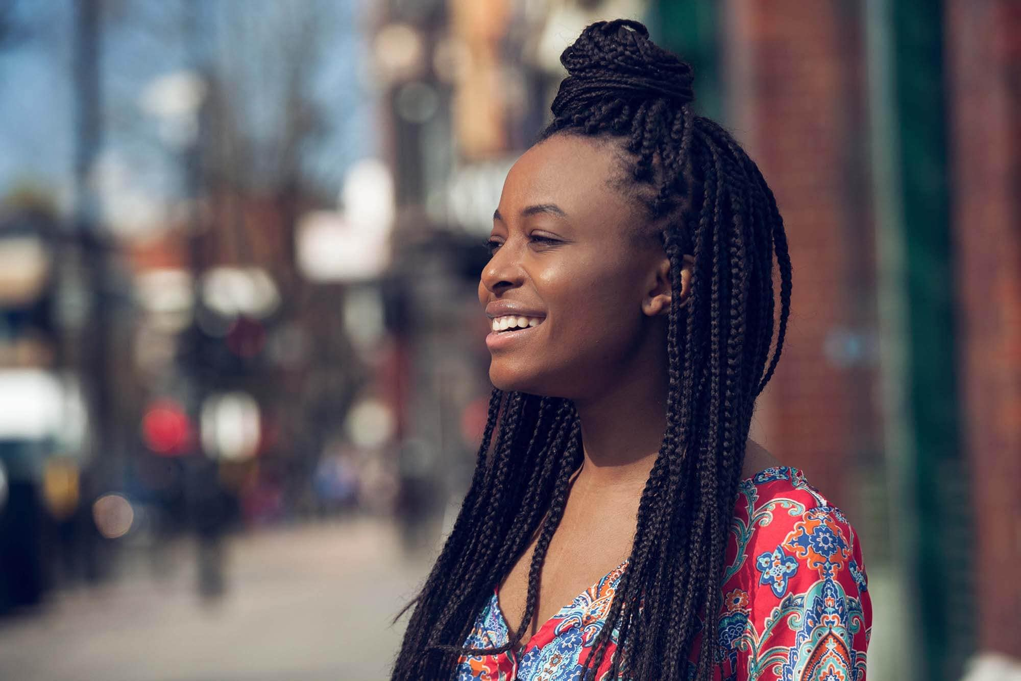 woman with long box braids in natural hair styled into a half up top knot
