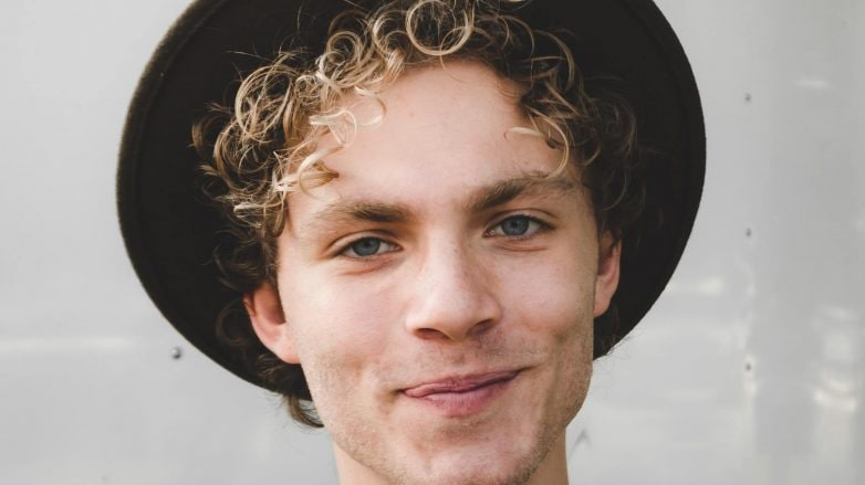 Man with curly blonde hair wearing hat and smiling