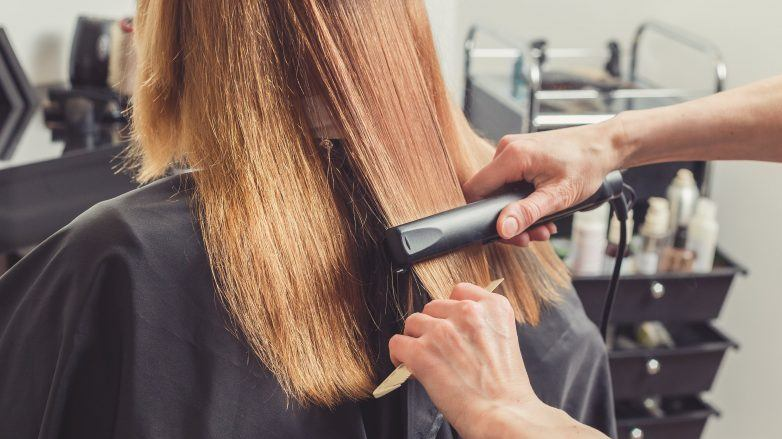 Woman getting hair hair straightened in a salon