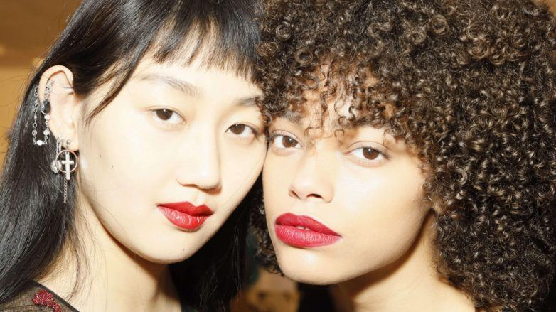 Two models backstage with straight and curly hair