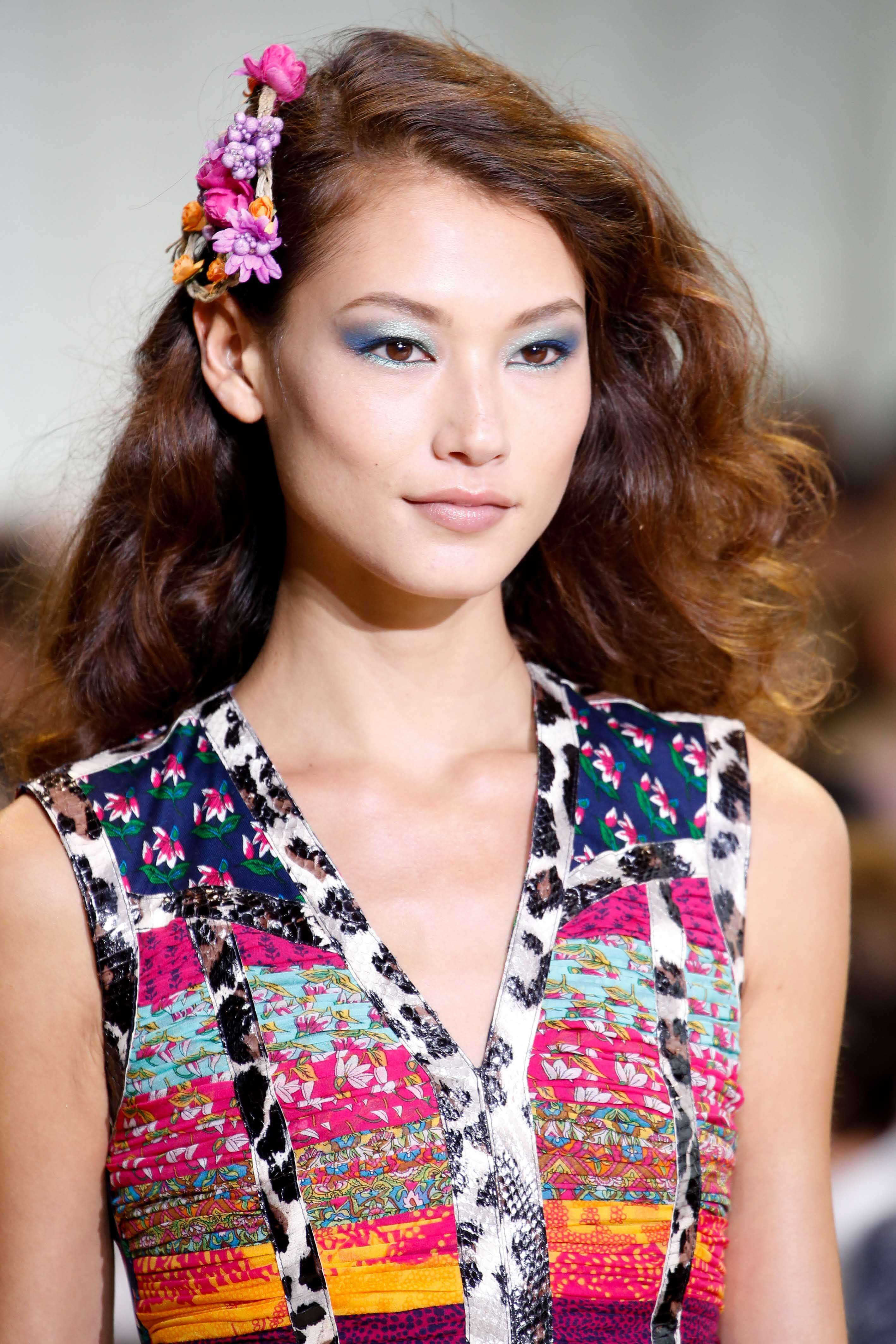 Asian hairstyles: Asian woman with golden caramel brown curly hair with floral hair accessory wearing a patterned dress.