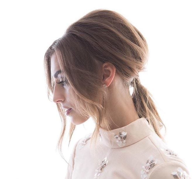 Elegant updos: side view of woman with light brown medium length straight hair styled into a '60s-inspired Bardot ponytail with long bardot bangs
